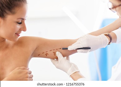 Plastic surgeon making marks on patient's body