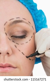 Plastic surgeon writing in the woman face in the white background