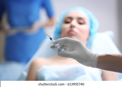 Plastic surgeon's hand holding syringe for facial injection with blurred patient on background