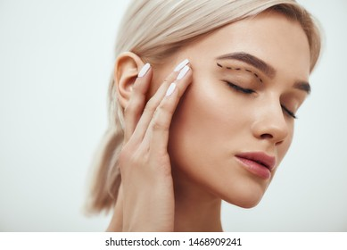 Plastic surgery. Beautiful young blonde woman keeping eyes closed and touching her face with sketch on it