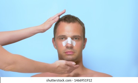 Plastic surgery concept, hands holding a man's face. a man after a plastic surgery on the face, rhinoplasty , with a bandage on the nose. on blue background.