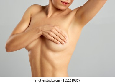 Plastic surgery of the female breast. Beautiful woman with naked torso examining breast mastopathy or cancer pressing on her nude breast.