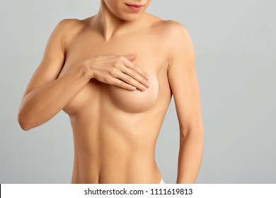Plastic surgery of the female breast.  Closeup cropped portrait young woman with breast pain touching chest colored isolated on background