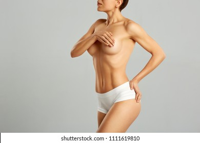 Plastic surgery of the female breast. Young woman with perfect tanned body. Portrait of female with perfect slim tanned body. Beauty and health care concept