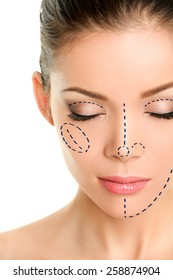 Plastic surgery lines on Asian woman face. Closeup of female adult with closed eyes with pencil marks on skin for cosmetic medical procedures. Surgical mark lines on eyes, nose, cheek, and jaw.