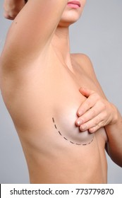 Plastic surgery. Naked woman covering her breast. Woman breast with dotted lines before breast augmentation operation
