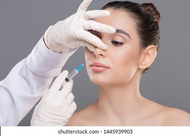 Plastic surgery of nose. Doctor filling injection into female nose, alternative rhinoplasty