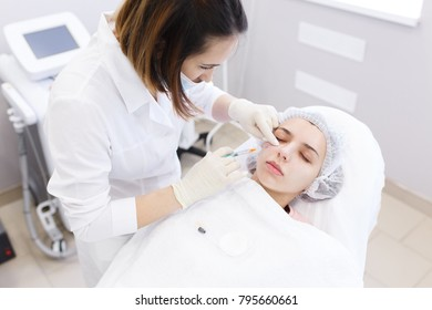Plastic surgery. Top view of portrait of patient and doctor doing biorevitalization of the face procedure in a beauty parlour clinic or spa salon.