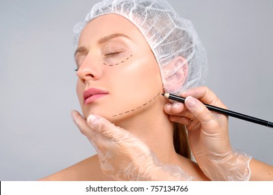 Plastic surgery. Woman with dotted lines on the face. Anti-aging treatment and face lift, doctor's hands drawing perforation lines on cheek