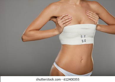 Plastic Surgery. Young Woman With Beautiful Slim Sexy Body Posing On Grey Background. Closeup Of Fit Female Patient Figure With Breast Covered In Medical Bandage. Cosmetology. High Resolution