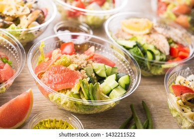 Plastic take away container with fresh salad consists of cucumber, avocado, tomato, grapefruit, on a wooden background. Tasty lunch food.