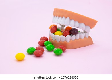Plastic teeth and dental model with colorful candy, Dental care concept