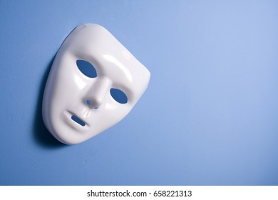 plastic theatral mask on blue wall
