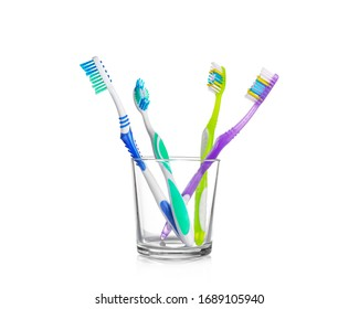 Plastic toothbrushes in glass on white isolated