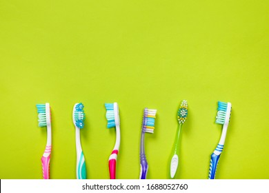 Plastic toothbrushes on green background