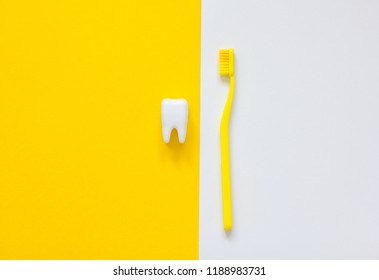 Plastic toothbrushes and white tooth on a yellow, white background. Dental care concept. Teeth care minimalism concept.