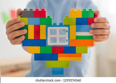Plastic toy blocks, designer of children's toys. Bright building blocks in the shape of a heart in children's hands. Educational toys. Early learning. Concept of love. Window to the heart. beneficence