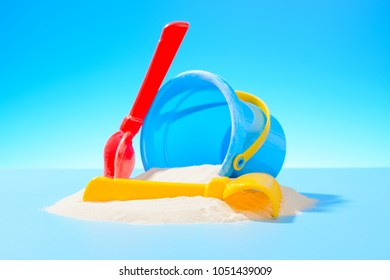 Plastic toy bucket, rake and shovel in the sand