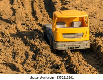 Plastic toy car on the sandbox. Children's toy car in playground. Yellow plastic truck on the sand – close-ups. Childhood concept. Making sand road in sandbox with toy car.