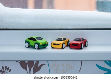 Plastic toy cars near snow-covered window, plays at home in winter