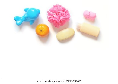 Plastic toy dolphin, mandarin, pink shower sponge, baby soap, shampoo bottle and toy hippo on a white background. Mockup for design, free space for text. Flat lay beauty products, spa cosmetics