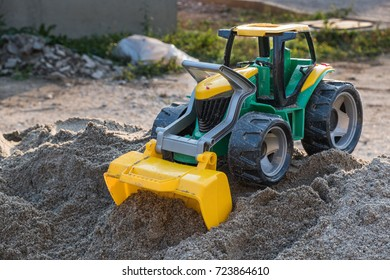 Plastic toy front loader placed on the top of the sand pile