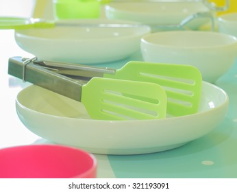 Plastic toy kitchen utensils and tableware toys on a table