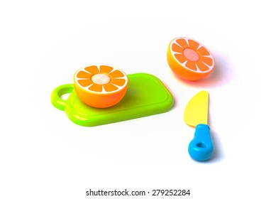 A plastic toy mikan orange on a cutting board being cut in half with a plastic knife.