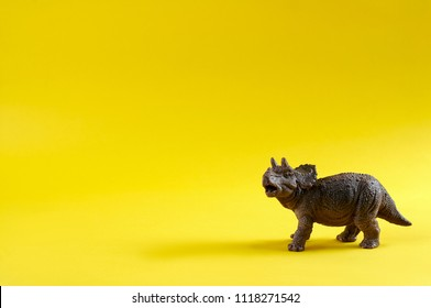 Plastic toy Triceratops dinosaur on yellow background. Copy space