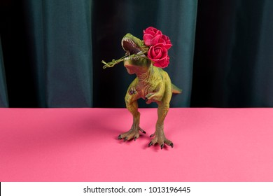 a plastic toy tyrannosaurus rex eating a bouquet of red roses on a vibrant green curtain and pink background. Minimal funny and quirky pop still life photography