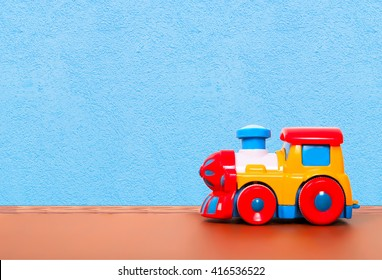 plastic train on the floor in a playroom