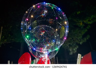Plastic transparent balloons with colourful lights at night