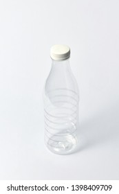 Plastic transparent empty bottle for dairy products, water and other liquid with white cup on a light gray background, mock up. Copy space.