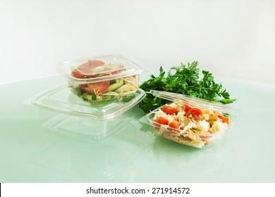 Transparente Kunststoffbehälter mit Salat auf Glastisch mit Grün