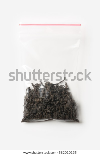 Plastic transparent zipper bag with a little black tea isolated on white, Vacuum package mockup with red clip. Concept