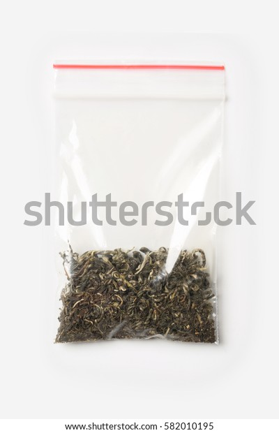 Plastic transparent zipper bag with a little dry green tea isolated on white, Vacuum package mockup with red clip. Concept