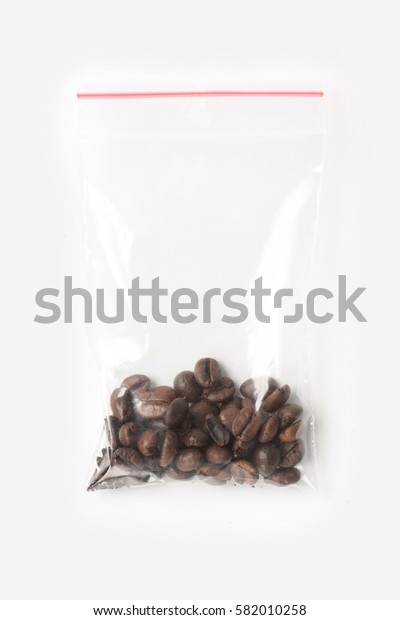 Plastic transparent zipper bag with a little wholegrain coffee beans isolated on white, Vacuum package mockup with red clip. Concept.