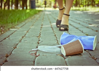 Plastic trash in the park with woman legs behind walking to pick up it