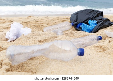 Plastic trash at the sandy beach. Plastic pollution concept. Single-use plastic is a human addiction that is destroying our planet and impacts our waters, sea life and humans.