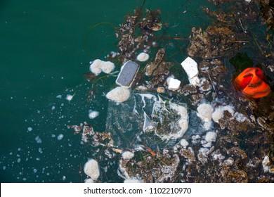 Plastic trash and sludge in harbor water.