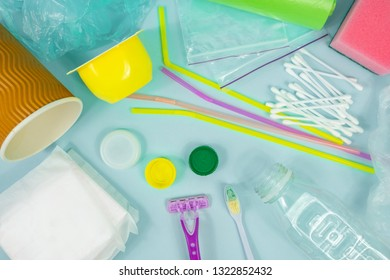 Plastic waste concept: variety of single use objects that get thrown out every day, top view. Plastic bottle, hygiene items and plastic package depicting ecological footprint of an everage person.