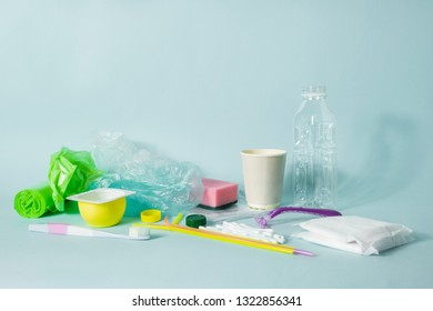 Plastic waste concept: variety of single use objects that get thrown out every day. Plastic bottle, hygiene items and plastic package depicting ecological footprint of an everage person.