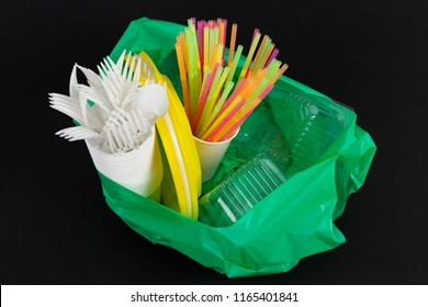 Plastic waste danger ecology concept with full garbage bag and colorful single use straws cutlery cups plates casserole boxes isolated on black background