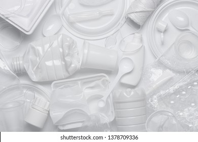 Plastic waste. Single-use plastic objects, ecological pollution. White packaging plastic products, top view flat lay.