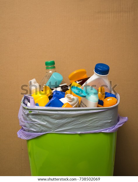 Plastic waste in the trash can in front of cardboard background