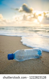 Plastic waste water bottle washed up in the waves on the shore of an empty tropical beach