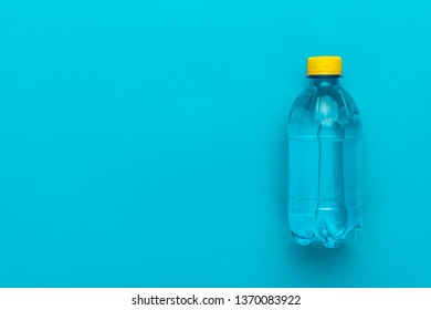 plastic water bottle with yellow cap on the blue background. minimalist photo of water bottle with copy space