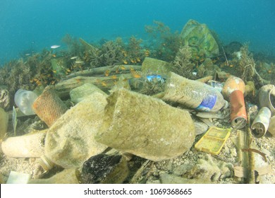 Plastic water bottles, bags and tins pollution on ocean floor