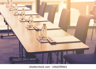 Plastic water bottles, Drinking glasses with pencil and white papers setup on the table prepared for seminar or business meeting in the hotel conference room