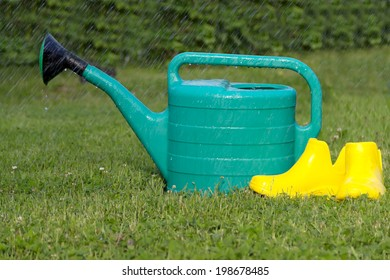 Plastic watering can yellow rubber boots mown lawn grass summer rain